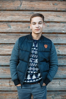 Cute charming young man with a beautiful smile with a hairstyle in a stylish jacket in a knitted new year's sweater in blue jeans stands against the wall of a wooden vintage wall. happy guy.
