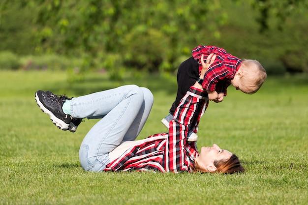 母とかわいい元気な赤ちゃんが公園で屋外抱擁します。家庭生活の幸福と調和。