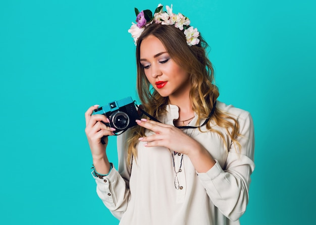 Cute cheerful blonde  fresh  woman with floral wreath on head posing  in spring stylish outfit  taking picture   on bright blue background.wearing tender floral wreath , spring   clothes.