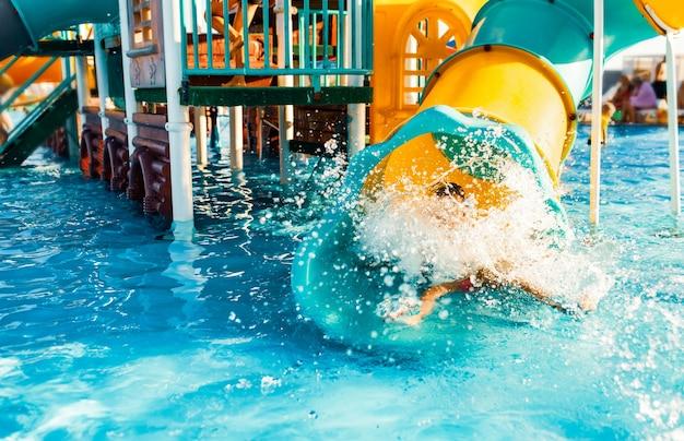 귀여운 쾌활한 아이가 밝은 노란색 슬라이드 터널에서 맑은 투명한 물이있는 수영장으로 내려와 물을 튀 깁니다.