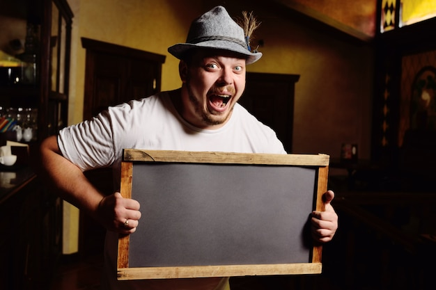 Cute cheerful fat man in a bavarian hat holding a chalkboard or a plate on the background of a pub