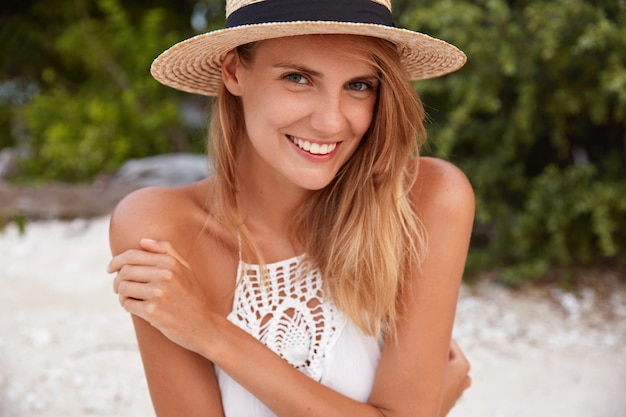 Cute cheerful female with shining smile and attractive look, wears summer dress and hat, demonstrates perfect tanned skin, poses on coastline with positive expression. people and vacation concept