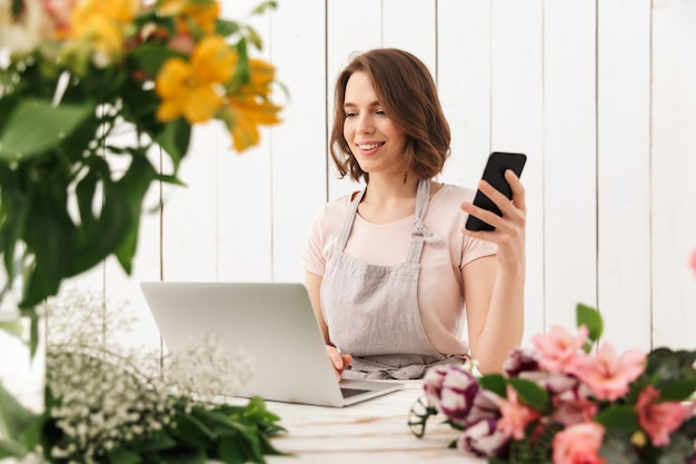 Cute cheerful florist lady using laptop computer chatting by mobile phone.
