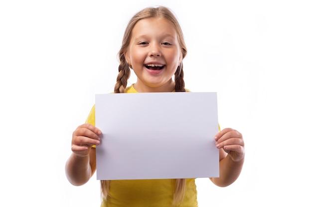 흰색 배경에 흰색 종이를 들고 변발에 땋은 금발 머리를 가진 귀여운 쾌활한 소녀.