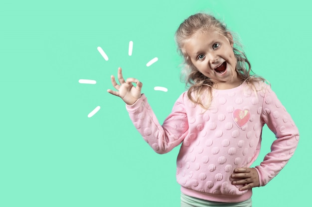 Cute cheerful girl with dimples and curly hair smiles and shows the ok sign on green