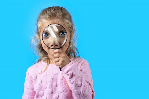A cute cheerful girl with dimples on her cheeks and curly hair looks through a magnifying glass on blue .