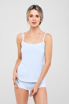 Милая жизнерадостная девушка со свежей чистой кожей смотрит в камеру в модной белой футболке и трусиках