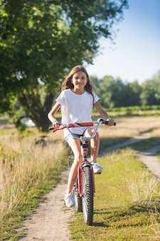 Cute cheerful girl with long hair riding her bicycle on dirt road at meadow