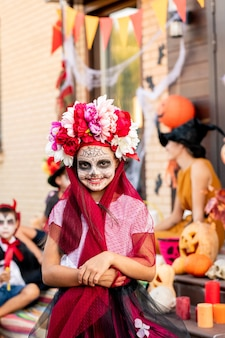 Cute cheerful girl with painted face looking at you with toothy smile while standing in front of camera against friends sitting on staircase