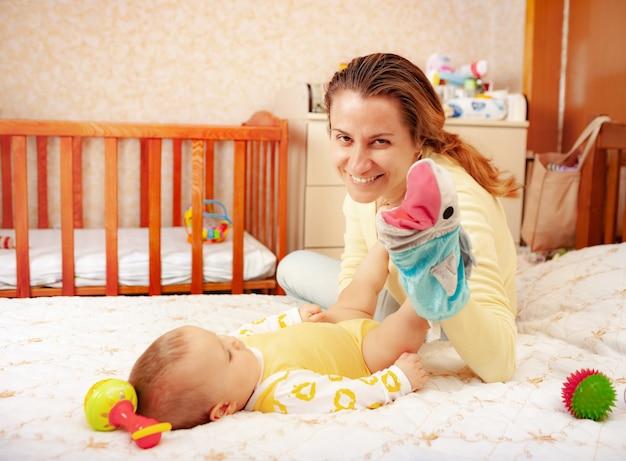 귀여운 쾌활한 친절한 어머니가 매력적인 6 개월 된 딸과 놀아요.
