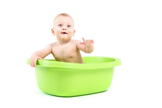 Cute cheerful little boy in green tub