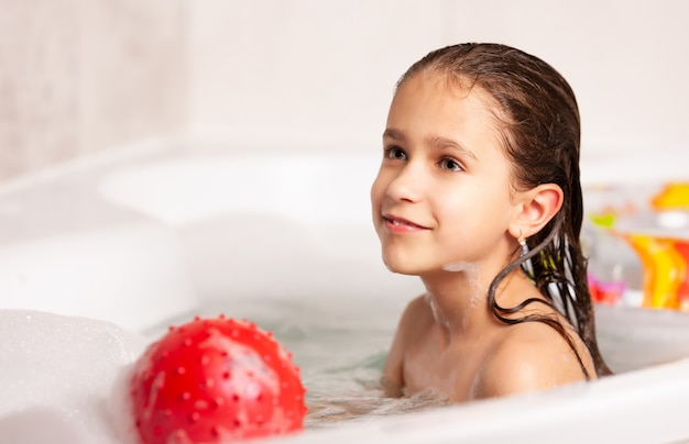Cute cheerful little caucasian girl bathes and plays the ball and rubber ring in the bathroom