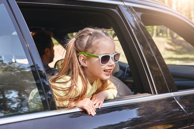 車の中に座って窓の外を見て笑っているかわいい陽気な小さな白人の女の子