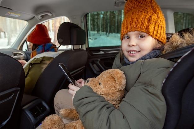 따뜻한 겨울옷을 입은 귀엽고 쾌활한 소녀가 차 뒷좌석에 앉아 부모님과 함께 여행하는 동안 이빨 미소로 당신을 바라보고 있습니다