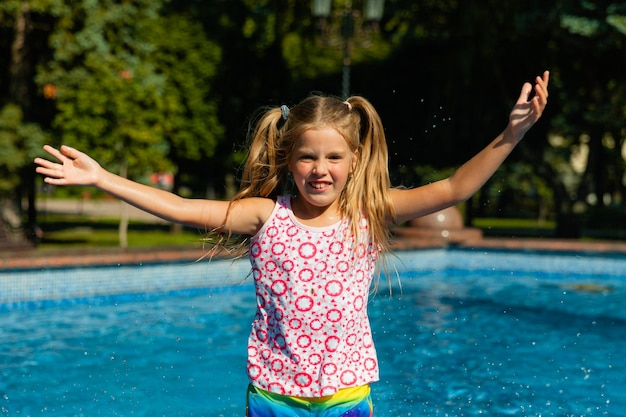 Милая веселая маленькая девочка играет в фонтане. ребенок веселится в летнем парке у городского фонтана.