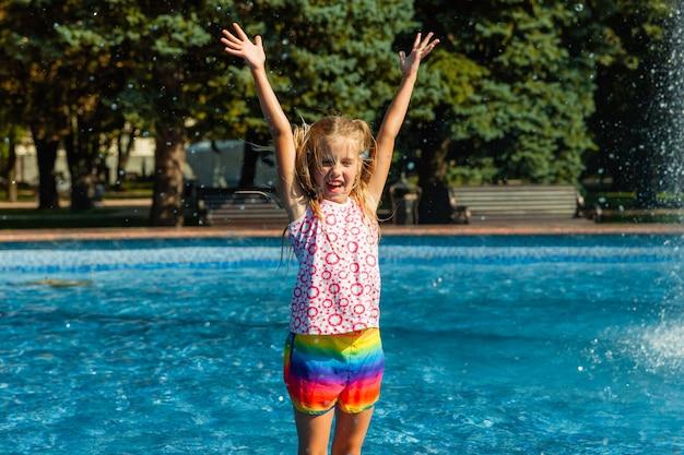 かわいい陽気な女の子が噴水で遊んでいます。子供は市の噴水のある夏の公園で楽しんでいます。