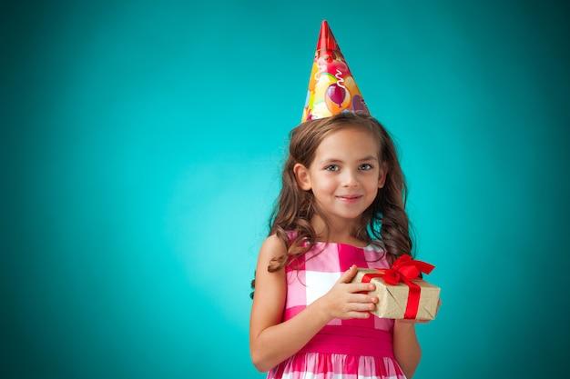 Милая веселая маленькая девочка на синем