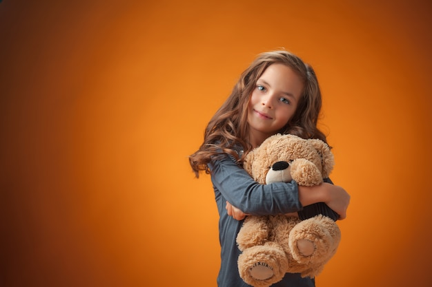 The cute cheerful little girl on orange background