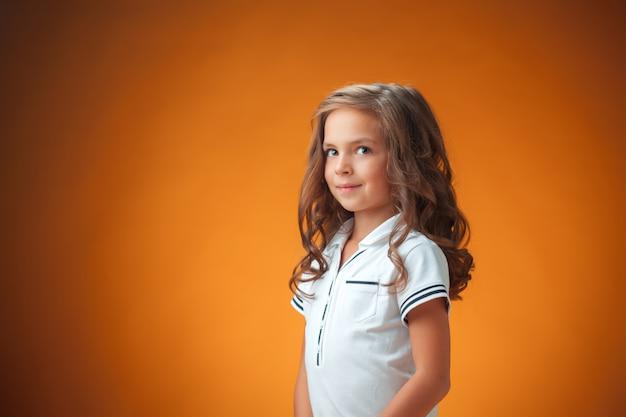 Cute cheerful little girl on orange