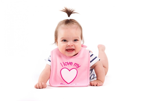 Cute cheerful little girl in pink  bib