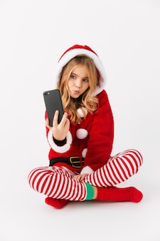 Cute cheerful little girl wearing christmas costume isolated, holding mobile phone, taking a selfie