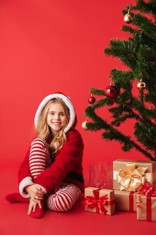 Милая жизнерадостная маленькая девочка в рождественском костюме изолирована, сидит у елки с стопкой подарков