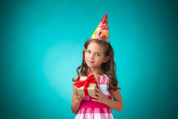La carina bambina allegra con regalo e cappello festivo su sfondo blu