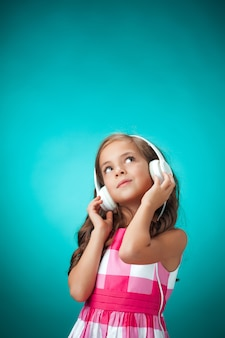 The cute cheerful little girl with headphones on orange wall