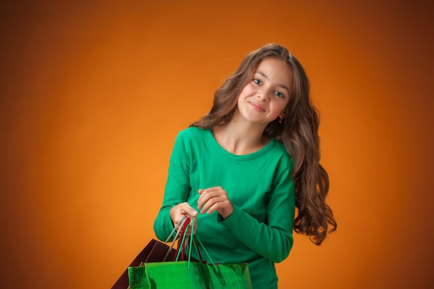 The cute cheerful little girl with shopping bags on orange background
