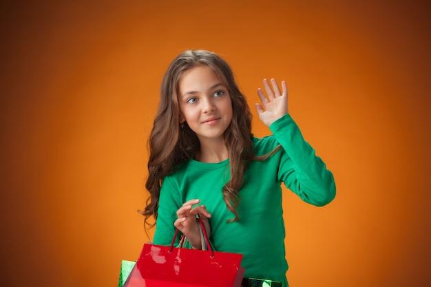 La graziosa bambina allegra con le borse della spesa