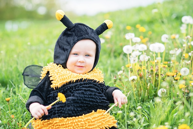 Cute and cheerful portrait of little child sitting in blooming flowers of dandelion in yellow bee costume.