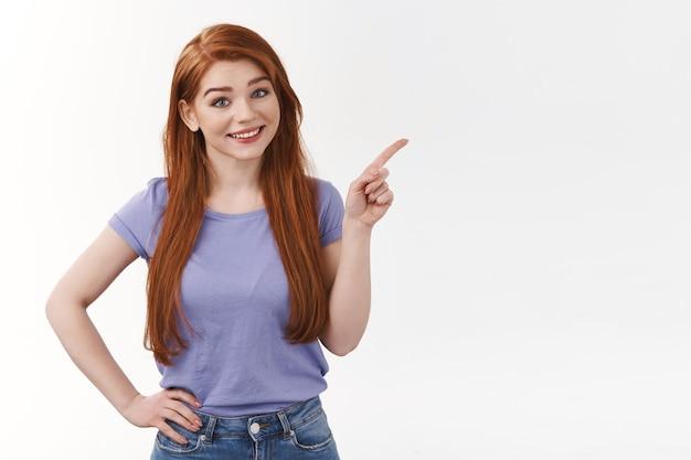 Симпатичная жизнерадостная рыжая женщина с длинными рыжими волосами, указывающая в правом верхнем углу, наклонив голову и улыбаясь, приглашая посетить профиль, интернет-магазин, указать корпоративный баннер, стоящая белая стена