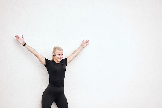 Милая жизнерадостная стройная женщина в черной спортивной одежде, слушает музыку и растягивается после тренировки.