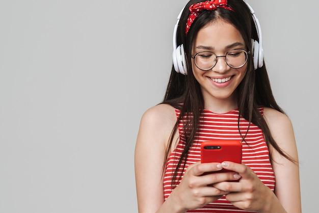 灰色の壁の上に孤立して立って、ヘッドフォンで音楽を聴いて、携帯電話を使用して、カジュアルな服を着てかわいい陽気な10代の少女