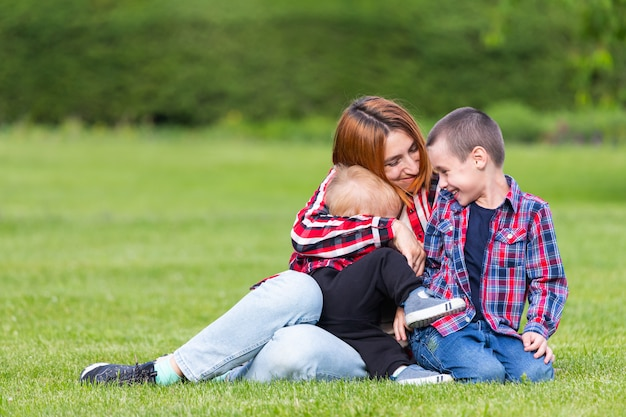 Cute cheerful two  boys brother child with mother play outdoors in park.