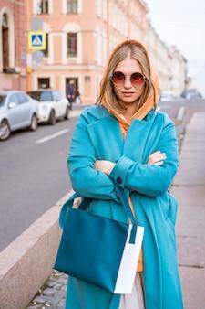 그녀의 손에 가방과 블루 코트와 오렌지 스웨터에 귀여운 쾌활한 여자는 봄 날에 도시를 산책