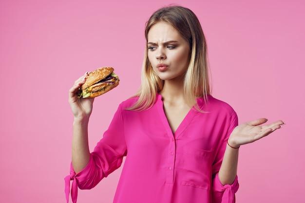 Милая веселая женщина в розовой рубашке, гамбургер, еда, диета