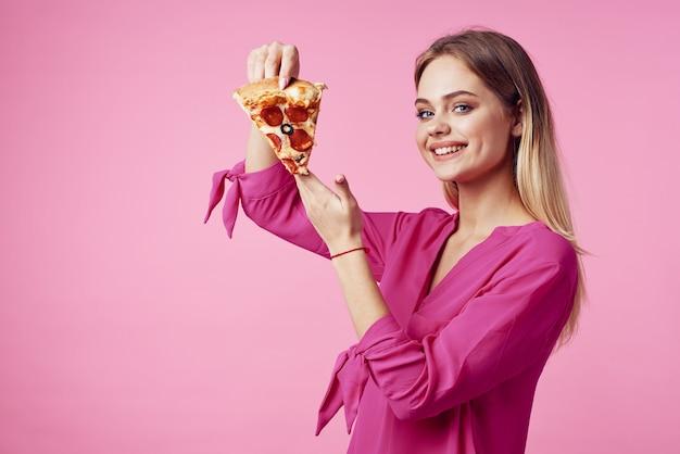 手でかわいい陽気な女性ピザスナックおいしいファーストフードピンクの背景