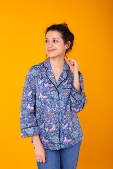 Cute and cheerful woman in pyjamas on orange wall