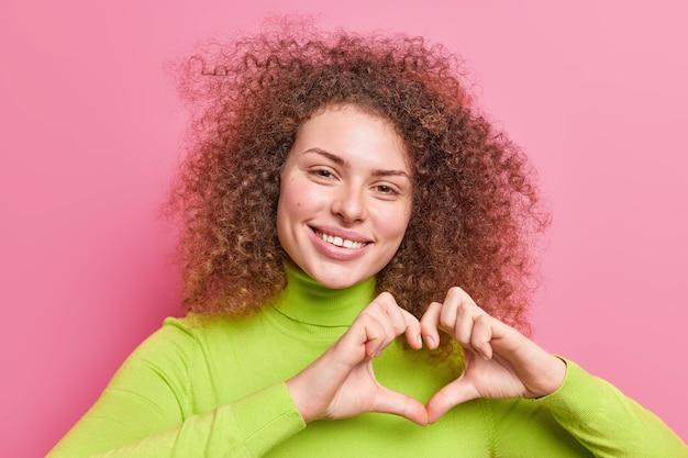 Симпатичная жизнерадостная женщина с вьющимися густыми волосами делает жест сердца влюбляется в вас, романтический взгляд выражает сочувствие, носит зеленую водолазку, изолированную над розовой стеной. будь моей валентинкой