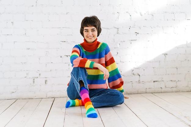 白いレンガの壁を背景に床に座っているカラフルなセーターのかわいい陽気な若い女の子...