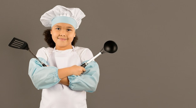 Cute chef holding cooking utensils