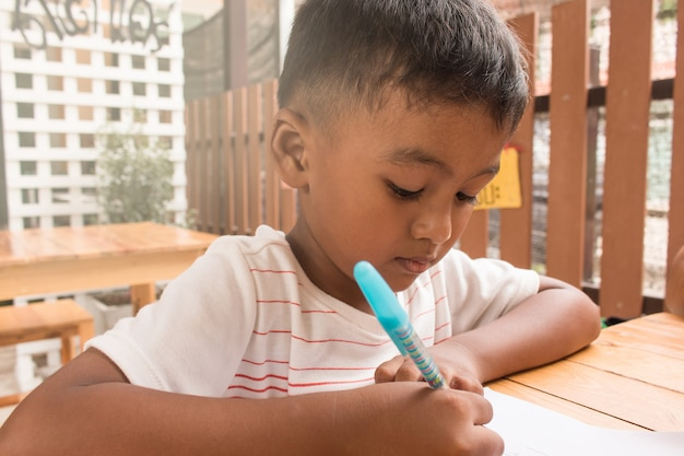 Cute child asian little boy doing homework on table