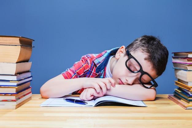 Милый ребенок спит за партой в школьной библиотеке. ученик в очках против многих книг