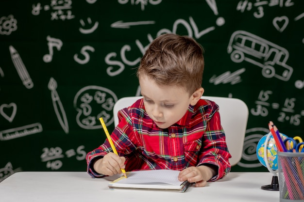 Cute child boy doing homework. clever kid drawing at desk. schoolboy. elementary school student drawing at workplace. kid enjoy learning. home schooling. back to school. little boy at school lesson