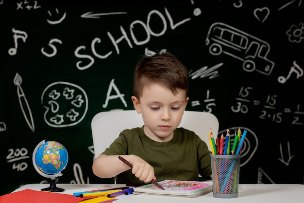 Cute child boy doing homework. clever kid drawing at desk. schoolboy. elementary school student drawing at workplace.