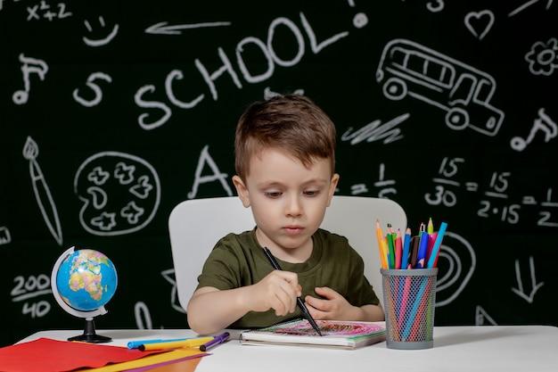 Милый ребенок мальчик делает домашнее задание.