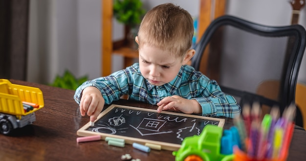 Cute child boy draws with chalk on blackboard at the table
