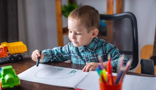 Cute child boy draws with chalk on paper in an album at the table