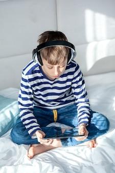 Милый ребенок мальчик в наушниках, играя на цифровом планшете на кровати в гостиной. образование, свободное время, технологии и концепция интернета